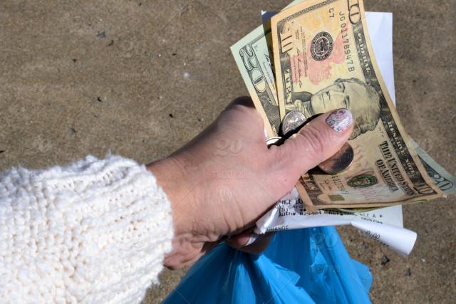 """Foto24 Mao segurando dinheiro Pesquisa: Maioria dos americanos pensa que os EUA estão na """"rota errada"""""""