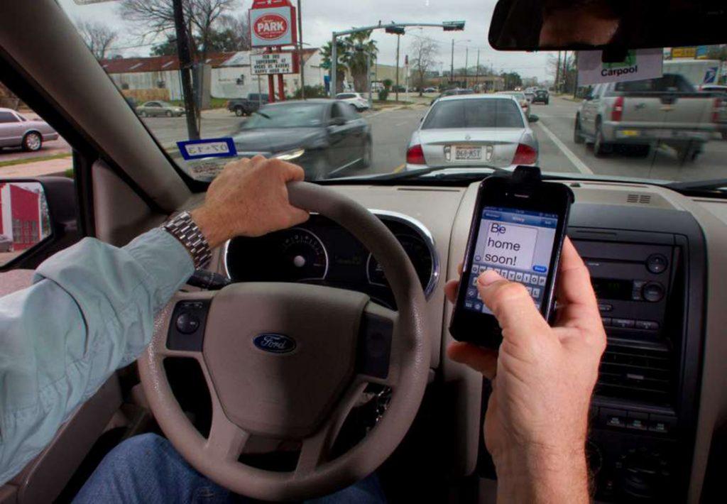 """Foto3 Dirigindo e enviando mensagem de texto  NJ: Combate a """"motoristas distraídos"""" começa na segunda (1)"""